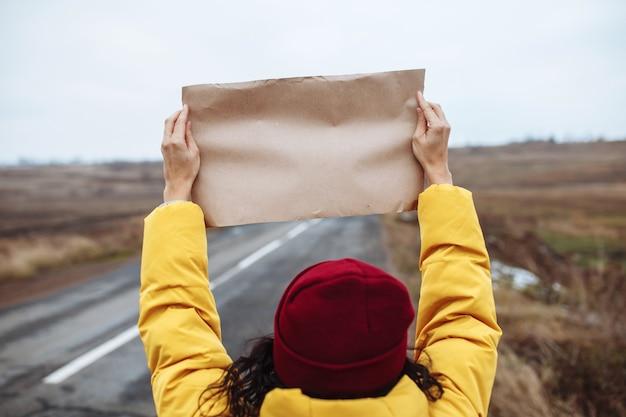 Backview van een vrouwentoerist die een gele jas en een rode hoed draagt, staat met een blanco posterpapier aan de kant van een lege winterweg.