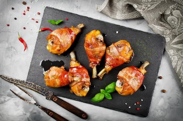 Bacon verpakte kippenbenen op een zwarte achtergrond