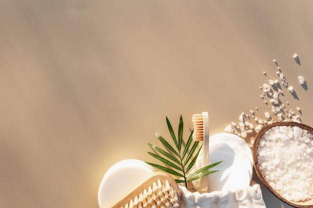 Badaccessoires plat leggen met zonneschaduweffect. gezondheidszorgconcept, houten tandenborstel, voetborstel, wattenschijfjes, zeep. eco, nul afval, herbruikbare, plasticvrije omgeving
