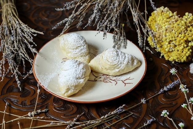 Badambura van zijaanzicht traditionele azerbeidzjaanse gebakjes op een plaat met bloemen op de lijst