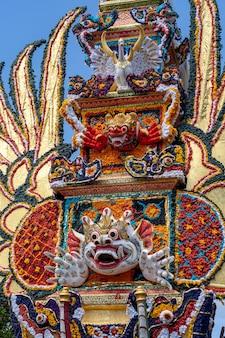 Bade crematietoren met traditionele balinese sculpturen van demonen en bloemen op centrale straat in ubud, eiland bali, indonesië. voorbereid voor een aanstaande crematieceremonie. detailopname