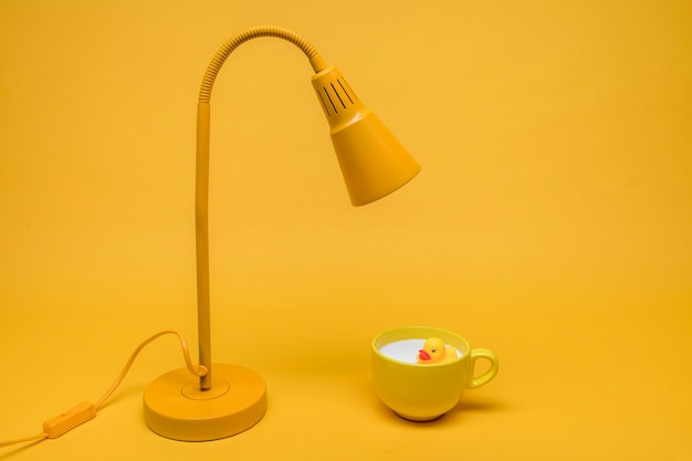 Badeend in een kopje melk onder een lamp