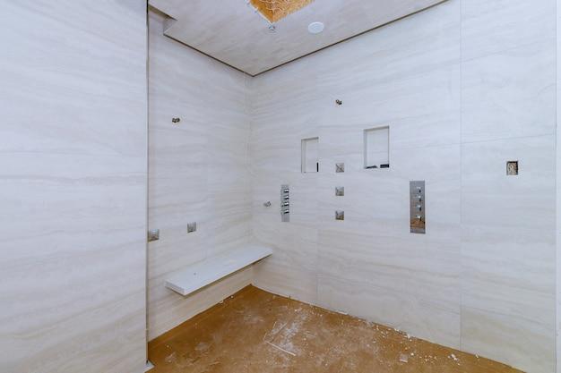 Badkamer met douche bedekt betegeld in het appartement dat in aanbouw is, verbouwing, restauratie en wederopbouw badkamermuur