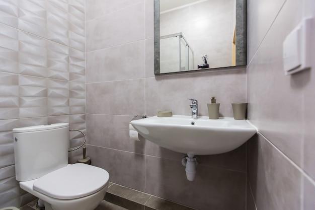 Badkamer met douche, ligbad en lichte tegels