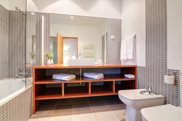 Badkamer met wastafel en bidet en handdoeken.