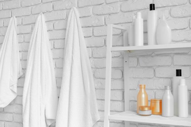 Badkamer rekken met cosmetische flessen en witte hangende handdoeken tegen witte bakstenen muur