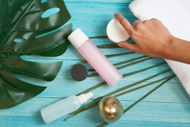 Badkameraccessoires cosmetica zeep groene bladeren blauwe houten achtergrond