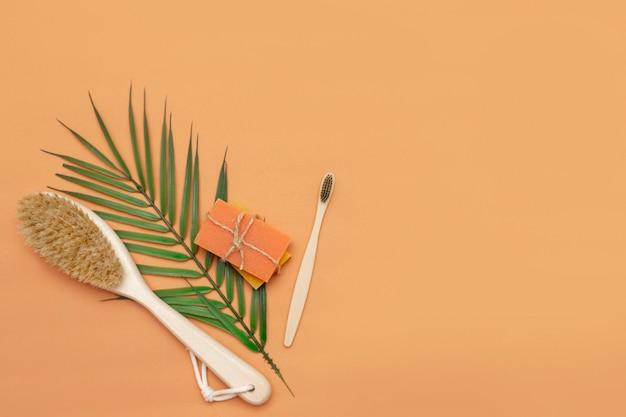Badkameraccessoires zonder afval, borstel met natuurlijke haren, houten tandenborstel, stukken vaste zeep met een palmblad op een beige achtergrond.