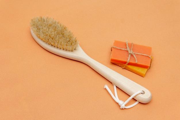 Badkameraccessoires zonder afval, borstel met natuurlijke haren, stukken vaste zeep, op een beige achtergrond