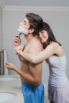 Badkamerroutine voor gelukkige jonge paar scheren in spiegel en vrouw knuffelen van achteren