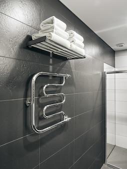 Badkamerstoilet en handdoekverwarmer in hotel met grijze muren en witte handdoeken