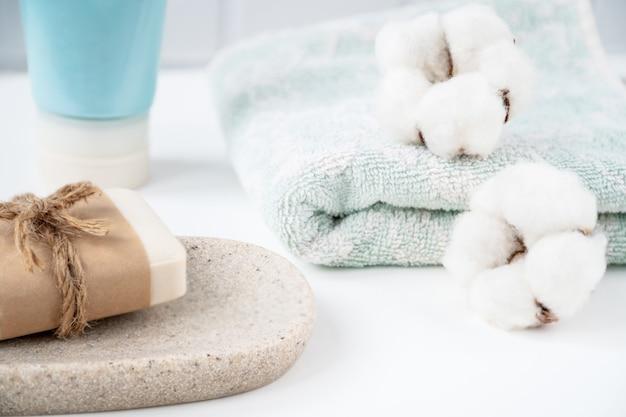 Badkamertafel met nieuwe zeepstaaf op dienblad en frisse schone handdoek versierd met pluizige wattenbolletjes
