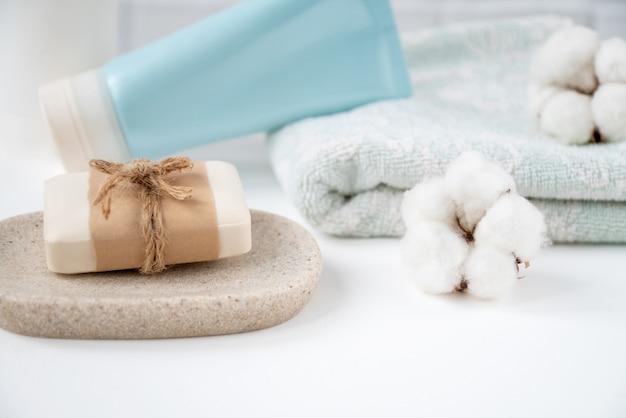 Badkamertafel met nieuwe zeepstaaf op dienblad, schone schone handdoek en tube cosmetica erop versierd met pluizige katoenen ballen.