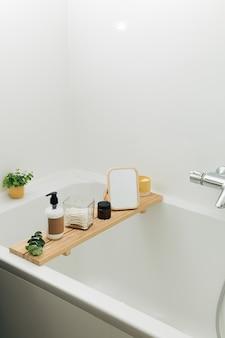 Badkuip houten dienblad met cosmetische schoonheidsflessen en accessoires in een moderne scandinavische badkamer met witte tegels als achtergrond. home decor met kaarsen en groene planten.
