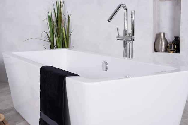 Badkuip in een badkamer met een handdoek erop en een kamerplant in de hoek