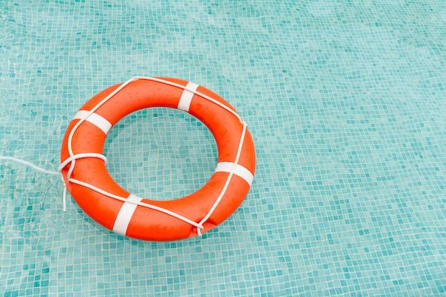 Badmeester die in zwembad drijft