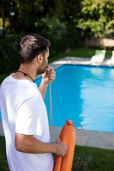 Badmeester fluitje blazen bij het zwembad op een zonnige dag