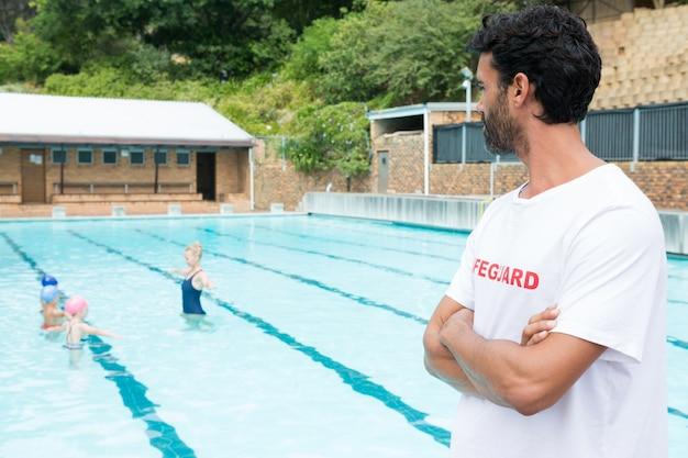 Badmeester kijken naar studenten spelen in het zwembad op een zonnige dag