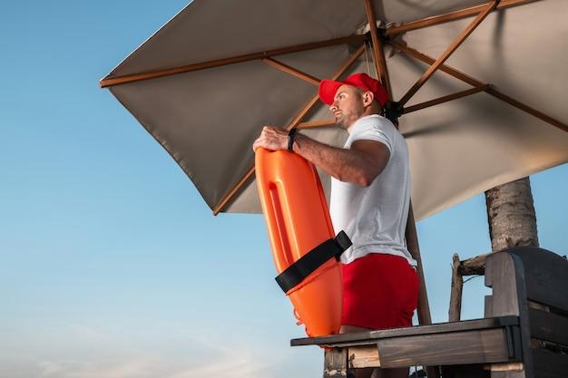 Badmeester met een oranje reddingsboei