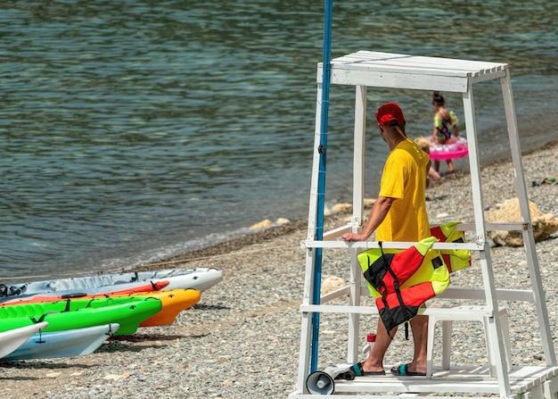 Badmeester op de toren kijkt naar het strand op de observatiepost voor houtredding op het strand