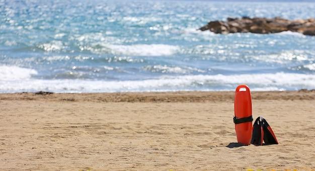 Badmeester reddingsuitrusting strand aan de zandzee met golven op de achtergrond