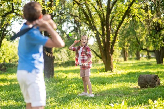 Badminton. extatische blonde schoolmeisje en jongen met rug naar camera badminton spelen in groen park op zonnige dag