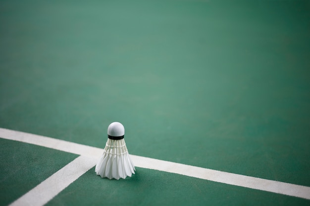 Badminton op de groene achtergrond van het badmintonhof