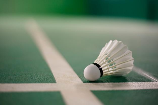 Badminton op de oranje lichte gloed van het badminton groene hof
