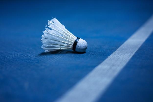 Badmintonbal dichtbij de lijn van het badmintonhof