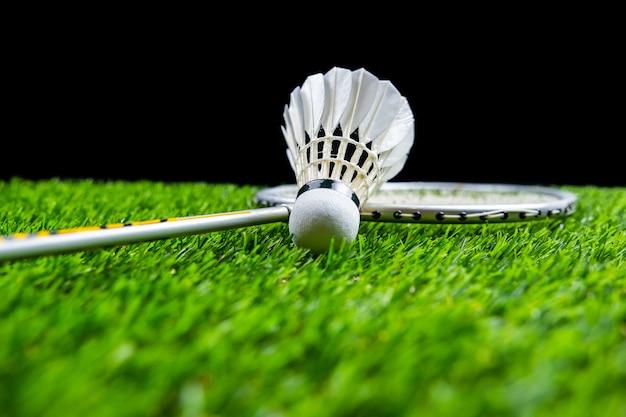 Badmintonbal en racket op gras op zwarte achtergrond