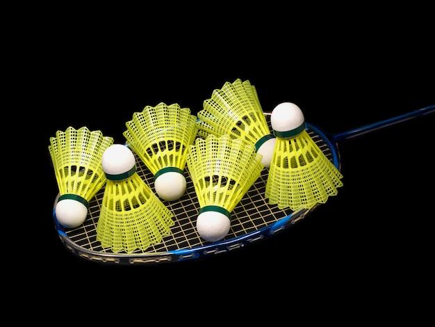 Badmintonracket en zes gele shuttles geïsoleerd op zwarte achtergrond