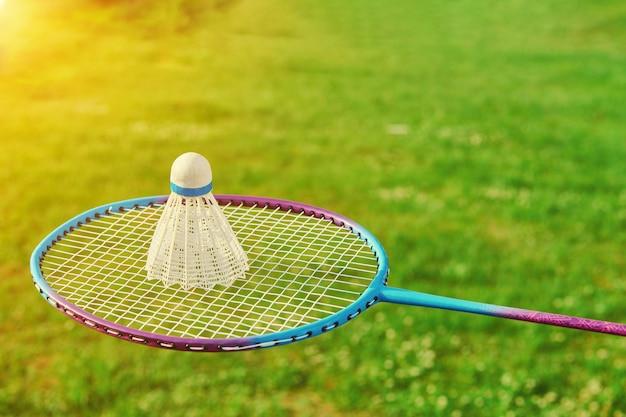 Badmintonracket met shuttle en groen gras. badminton openluchtspelactiviteit. badminton buitensport spelen. close-up bekijken met kopie ruimte.