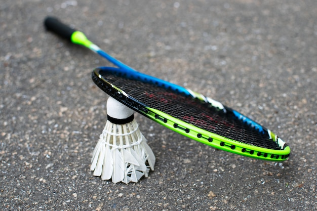 Badmintonrackets en shuttle op asfalt