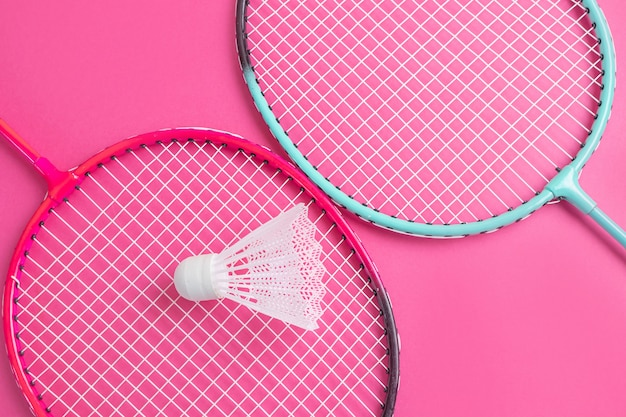 Badmintonrackets en shuttle op een felroze.