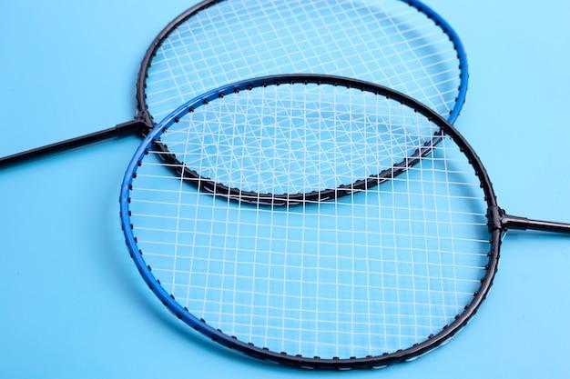 Badmintonrackets op blauwe achtergrond.
