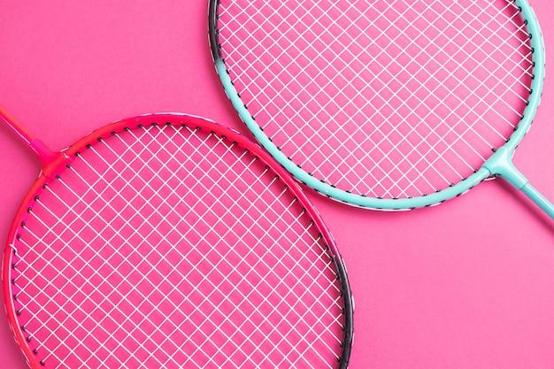 Badmintonrackets op een felroze.