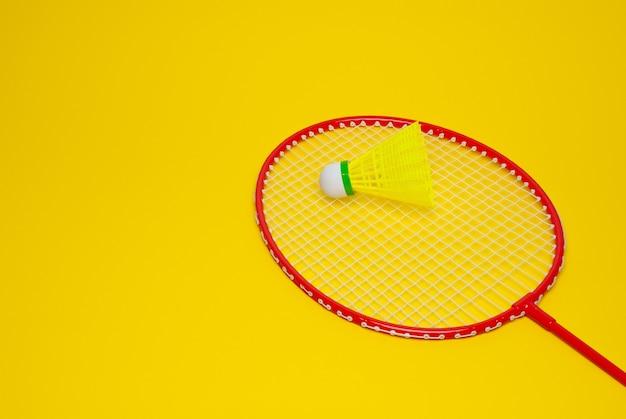 Badmintonshuttle en racket geïsoleerd op geel