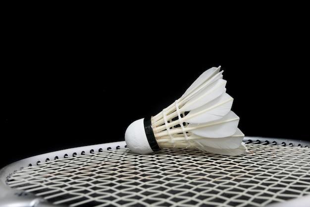 Badmintonshuttle en racket op gras en zwarte achtergrond