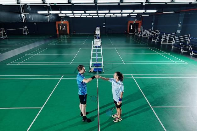 Badmintonspelers trainen in de gymzaal