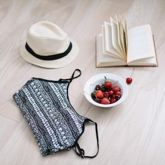Badpak, hoed, boek en verse zoete kersen en aardbeien op houten vloer