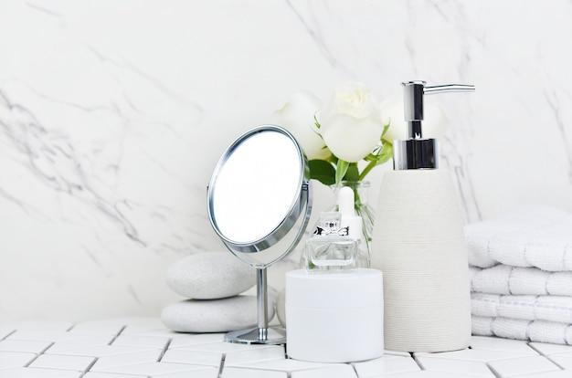 Badproducten in de badkamer, spa shampoo, douchegel, vloeibare zeep met een handdoek ernaast en diverse accessoires