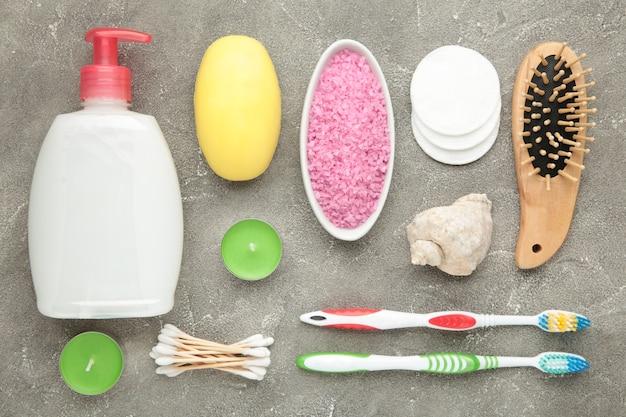 Badproducten op grijze muur. douchegel met aromatisch zout, zeep en andere toiletspullen. bovenaanzicht