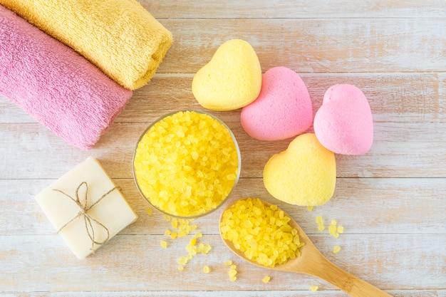 Badspa-accessoires met badbommen in de vorm van hart, zeezout, handdoeken en handgemaakte zeep