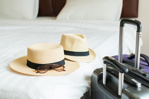 Bagage en hoed van een paar op bed in moderne hotelkamer met ramen, gordijnen. reis-, ontspannings-, reis-, reis- en vakantieconcepten. detailopname
