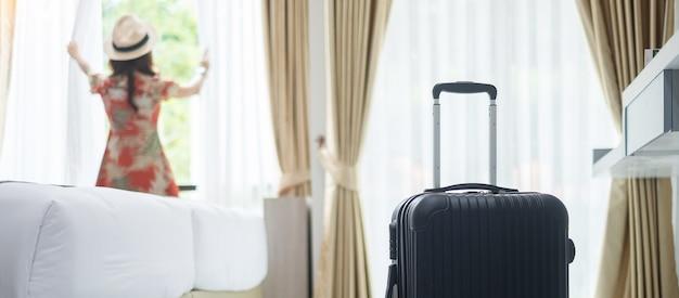 Bagage in moderne hotelkamer met gelukkig jong volwassen wijfje die bijna venster ontspannen, aziatische vrouwentoerist die aan mooi aardmening kijken. tijd om te reizen, ontspanning, reis, reis en vakantieconcepten