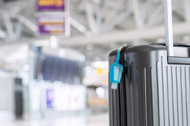 Bagagezak met alcoholgel handdesinfecterend middel in internationale luchthaventerminal, bescherming tegen coronavirus (covid-19) infectie. nieuwe normale en reisballonconcepten