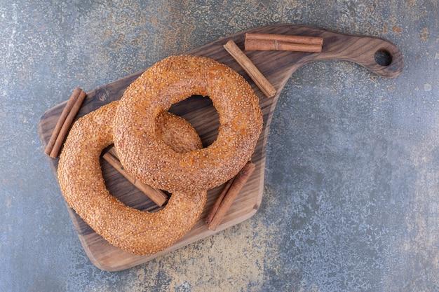 Bagels en kaneelstokjes op een houten bord op marmeren oppervlak