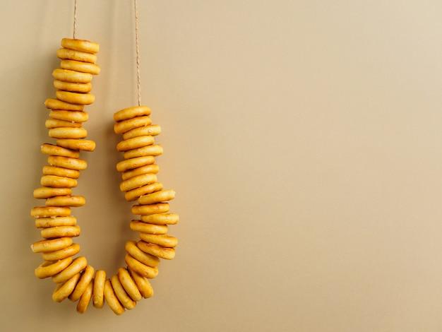 Bagels hangen aan een touwtje aan de gele muur.