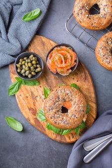 Bagels met gerookte zalm, roomkaas en kappertjes op een tafel. eten, lunch, brunch, maaltijd op een bord, plateren concept. plat lag, bovenaanzicht.