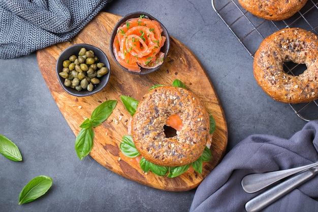 Bagels met gerookte zalm, roomkaas en kappertjes op een tafel. voedsel, lunch, brunch, maaltijd op een bord, platerenconcept